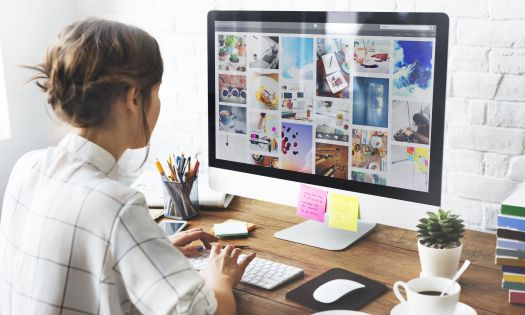 Best photo management software: Girl sitting on desk organizing photos on a Mac computer
